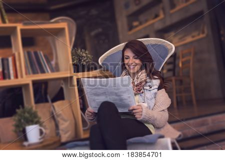 Young woman sitting in a cafe reading newspapers
