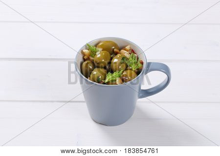 cup of marinated green olives on white wooden background