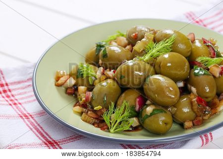 plate of marinated green olives on checkered dishtowel - close up
