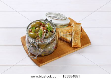 jar of marinated green olives and toasts on wooden cutting board