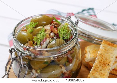 jar of marinated green olives and toasts on wooden cutting board - close up