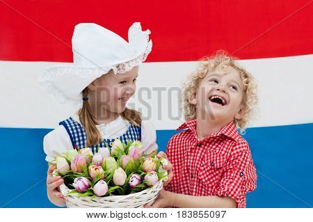 Dutch Kids With Tulip Flowers And Netherlands Flag