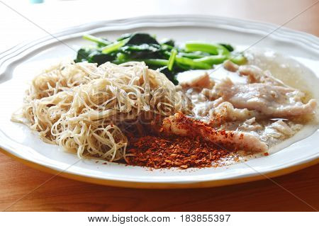fried thin rice noodle dressing pork gravy sauce on dish