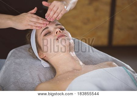 Young Woman During Face Salt Scrub Therapy