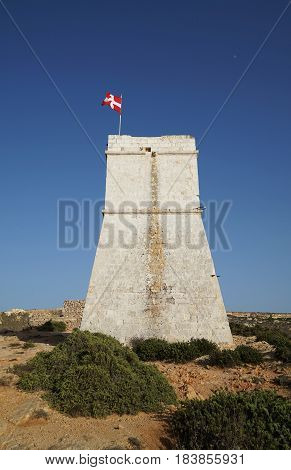 Lonely watchtower with maltese flag on the blue sky background