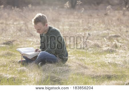 Man reading Bible in open field outdoors