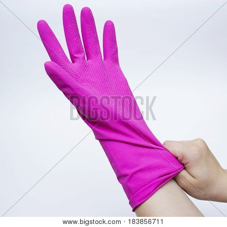 A young adult man's right hand stretching a disposable blue latex glove on his left hand. Isolated on white background.