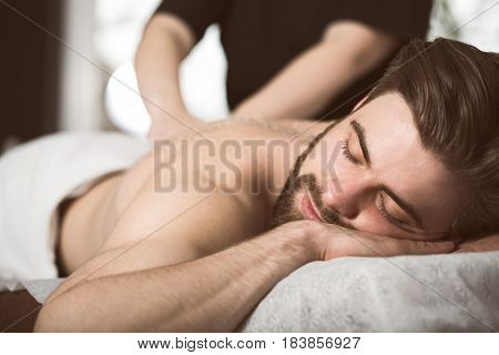 Man Relaxing During A Salt Scrub Beauty Therapy