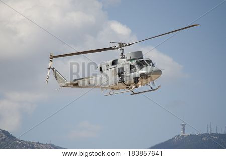 Black hawk helicopter rescue team,approach landing. right machine gun view. mountain background with aviation antenna