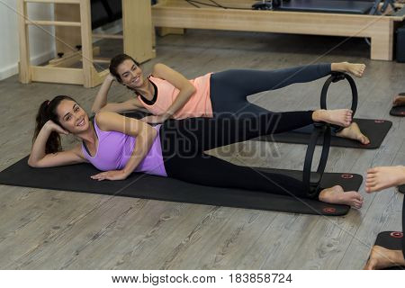 Portrait of two fit women exercising with pilates ring in gym