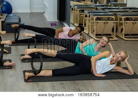 Portrait of smiling fit women exercising with pilates ring in gym