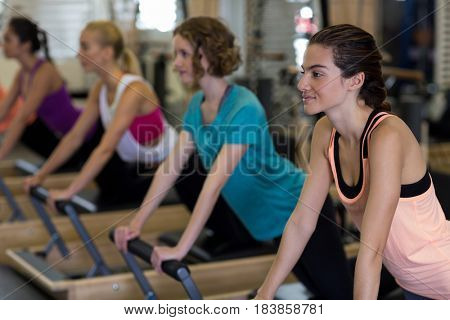 Group of women exercising on reformer in gym