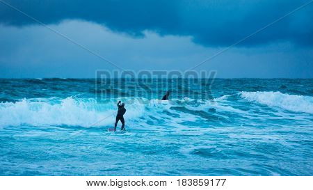 Surfer are training on the Skagsanden beach of the Lofoten Islands