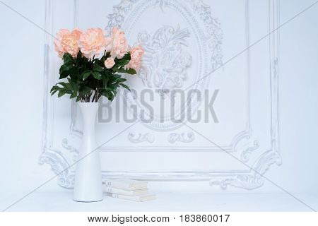 Artificial pink peonies in a white vase next to white books. Composition of flowers in a white vase