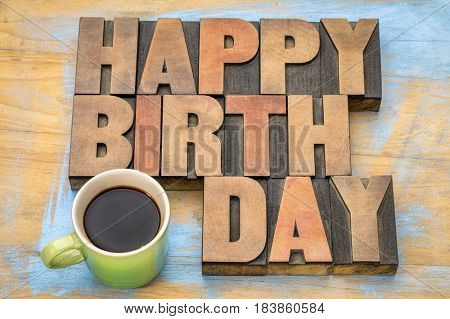 Happy Birthday word abstract - a greeting card in vintage letterpress wood type blocks with a cup of coffee