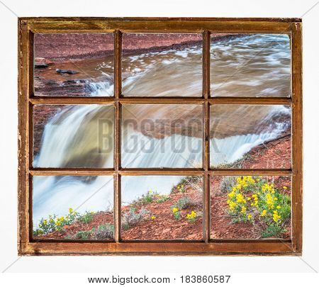 creek waterfall with wildflowers as seen  through vintage, grunge, sash window with dirty glass