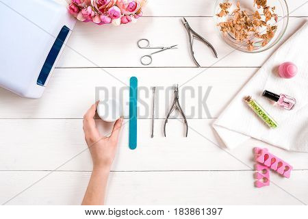Manicure set and nail polish on wooden background. Top view. Copy space. Still life. Nail Care.