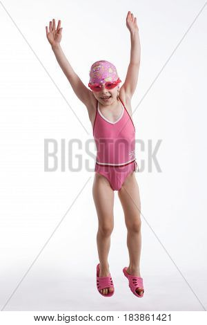 Little girl jumping in a pink swimsuit