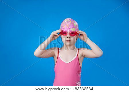 A girl in a pink bathing suit, swimming goggles and a swimming cap