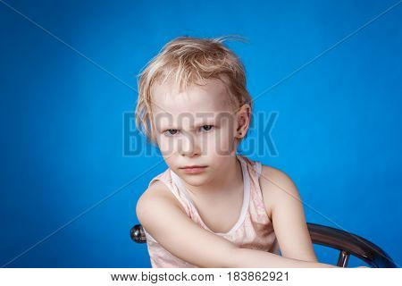 Angry child looks at the camera on a blue background