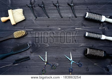 Hairdresser tools on wooden background. Top view on wooden table with scissors comb hairbrushes and hairclips free space