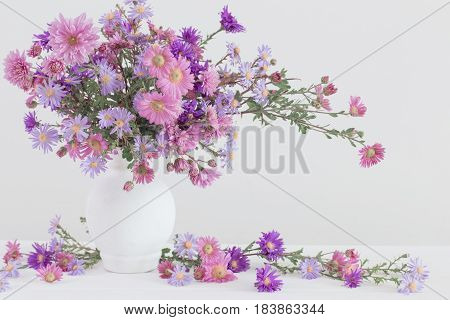 Aster amellus bouquet in ceramic vase on white background