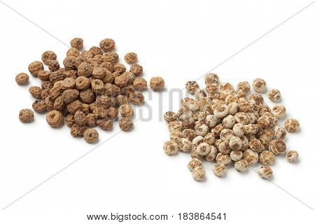 Heap of shelled and unshelled Chufa nuts on white background