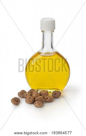 Glass bottle with Chufa oil and nuts on white background