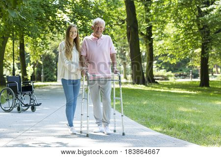Senior Man With Walking Frame Accompanied By Caregiver