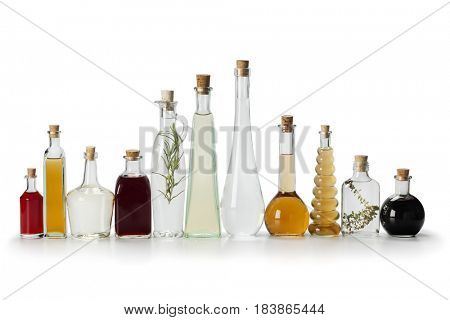 Row of bottles with homemade organic vinegar on white background