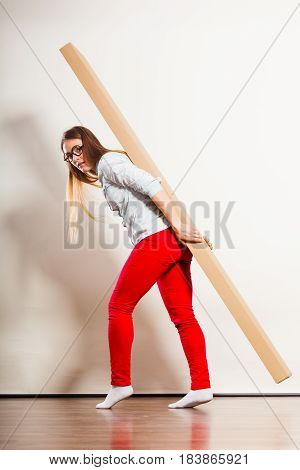 Woman Moving Into Apartment Carrying Heavy Box.