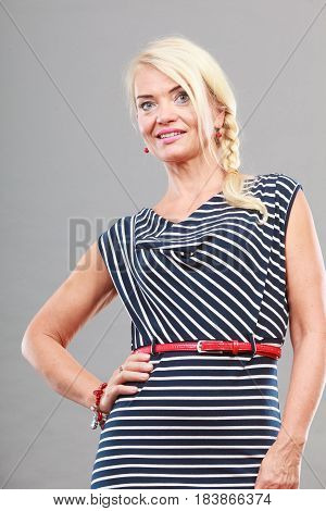 Mid adult blond attractive woman iwearing striped dress posing studio shot on gray