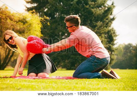 Love and dating. Young fashionable couple lovers having fun with big red heart in park.