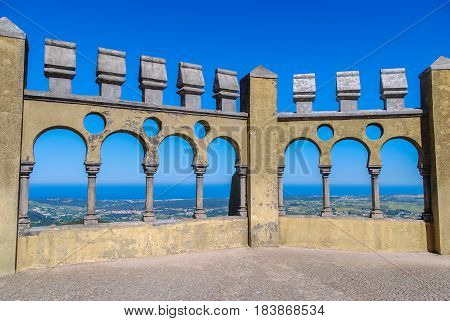 Castle balcony with arched portals and panoramic view of forests and ocean in the background