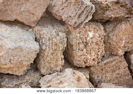 Pile of textured coquina blocks. Sand bricks with spongy surface made of fossil corals sponges shells. horizontal shot