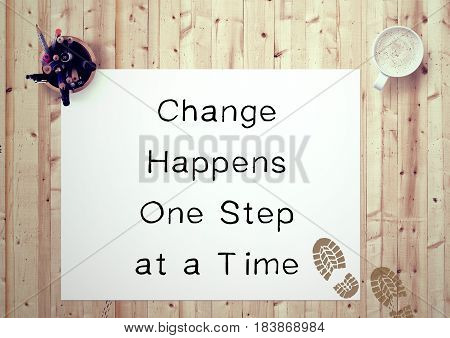 Inspiring motivation quote handwritten on a note pad change happens one step at a time. White pad paper image.