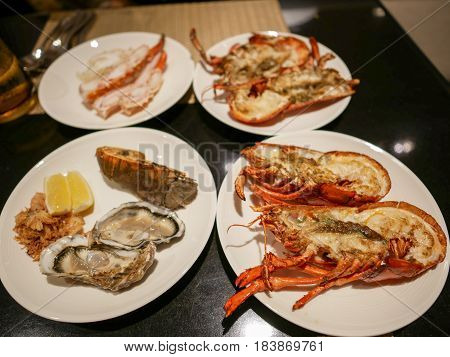 Giant grilled river prawns Rock Lobster Oysters and Crab legs on the white dishes.