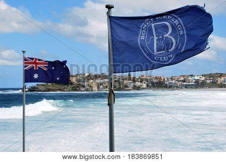 SYDNEY, AUSTRALIA - NOVEMBER 03, 2014: Bondi Icebergs Club branded flag and national Australian flag are waving on the background of blue sky at Bondi Beach