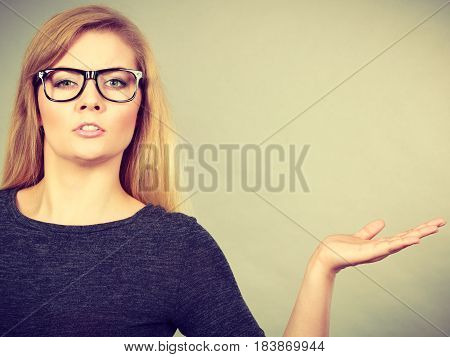 Nerdy woman in big eyeglasses having confused face expression pointing with palm open hand