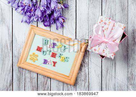 Beautiful bouquet of crocuses flowers gift box and frame with colorful wooden letters spelled Happy Mother's Day on the rustic wooden boards.