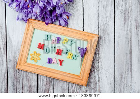 Beautiful bouquet of crocuses flowers and frame with colorful wooden letters spelled Happy Mother's Day on the rustic wooden boards.