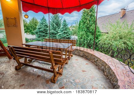 Patio of family home. Wooden table with benches. A swing