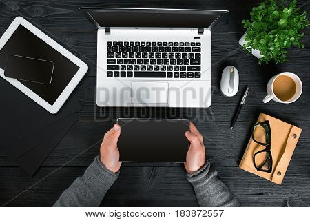 Hipster black wooden desktop top view, male hands typing on a laptop. Top view. Copy space