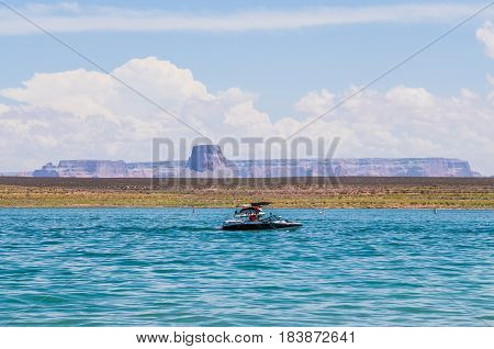 Sunny day at Lake Powell with boat and canyons in clear water