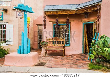 Albuquerque USA - July 28 2015: Old town plaza at hidden patio with San Pasquals shop and decorative sidewalk with brick paths flowers dried chiles and gardens