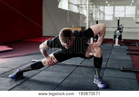 Young man preparing muscles before training. Muscular athlete exercising. Fit man stretching. Professional sportsman warming-up