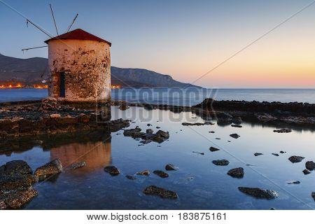 Sunrise landscape with a windmill in Agia Marina village on Leros island in Greece.