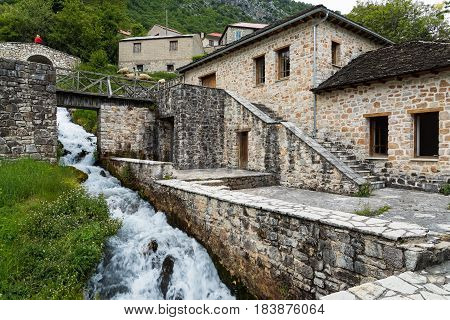 Traditional stone houses and two small bridges near a small cascade in Anthochori village in Epirus, Greece