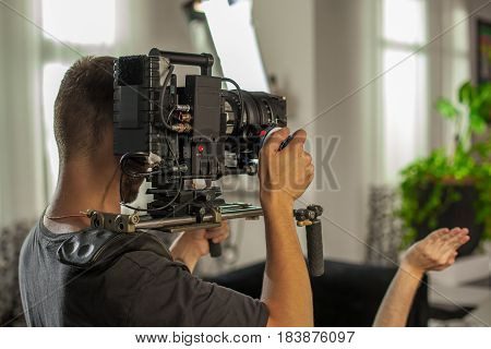 Videographer shoots clip for famous star indoors. Professional camera