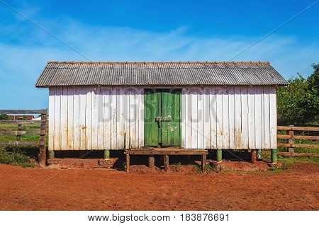 Outdoors of a suspended farm old house. Rustic house made of wood dirt white walls green door on farm scenario.